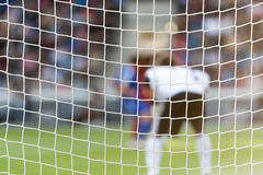 Goalkeeper behind football net Royalty Free Stock Image