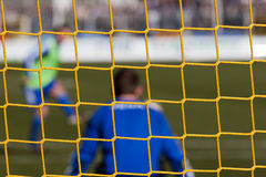Goalkeeper behind soccer net Stock Photography