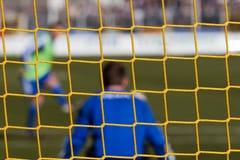 Goalkeeper behind soccer net stock photography