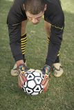 Goalkeeper bending down with ball Stock Photography