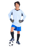 Goalkeeper in blue holding ball with foot Royalty Free Stock Images