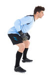 Goalkeeper in blue ready to save. On white background stock photography