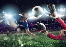 Goalkeeper catches the ball in the stadium during a football game. royalty free stock image