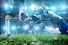 Goalkeeper catches the ball in the stadium during a football game. stock photos