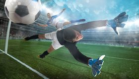Goalkeeper catches the ball in the stadium during a football game. Football close up scene at the stadium stock image
