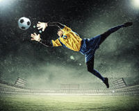 Goalkeeper catches the ball. At the stadium, in the spotlight Royalty Free Stock Image