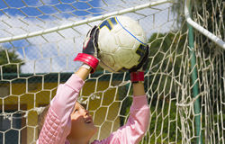 Goalkeeper child blocking the ball Stock Photo
