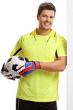 Goalkeeper with a football leaning against a wall. Isolated on white background stock photos