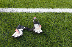 Goalkeeper gloves in the grass on the football field.  Royalty Free Stock Image