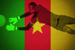 Goalkeeper in green making a save. Against cameroon national flag royalty free stock image