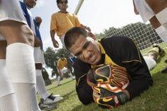 Goalkeeper on ground holding soccer ball Stock Image