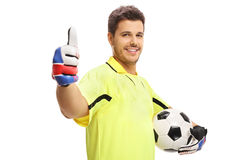 Goalkeeper holding a football and making a thumb up sign Royalty Free Stock Photography
