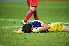The goalkeeper lies on the ground clutching the ball. The goalkeeper lies on the ground clutching the ball in competition stock photography