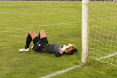 Goalkeeper missed the goal and lies near the gate Royalty Free Stock Photos
