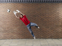 Goalkeeper Reaching For Football Against Brick Wall Stock Images