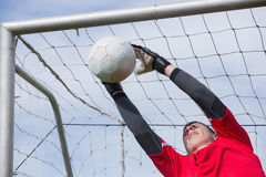 Goalkeeper in red jumping up to save a goal Royalty Free Stock Image