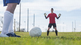 Goalkeeper in red waiting for striker to hit ball Royalty Free Stock Images