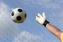 Goalkeeper's hands reaching for foot ball Royalty Free Stock Photos