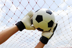 Goalkeeper's hands reaching for foot ball Royalty Free Stock Photography