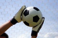 Goalkeeper's hands reaching foot ball Stock Photography