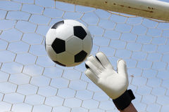 Goalkeeper's hands reaching foot ball Royalty Free Stock Images