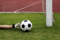 Goalkeeper's hands reaching foot ball Royalty Free Stock Photography