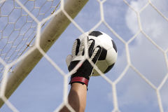 Goalkeeper's hands reaching foot ball Royalty Free Stock Photos
