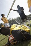 Goalkeeper with soccer ball, referee in background Royalty Free Stock Photo