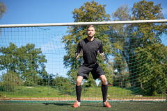 Goalkeeper or soccer player at football goal. Sport and people - soccer player or goalkeeper at football goal on field Royalty Free Stock Image