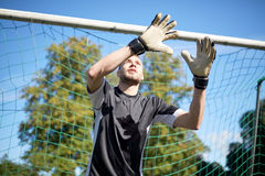 Goalkeeper or soccer player at football goal. Sport and people - soccer player or goalkeeper at football goal on field Royalty Free Stock Photos