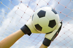 Goalkeeper used hands for catches the ball Stock Photo