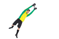 Goalkeeper in yellow jumping up. On white background stock image