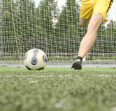 Goalkeeper in the yellow shorts. Kicking ball much out of the gate - focus on the soccer ball Royalty Free Stock Photos