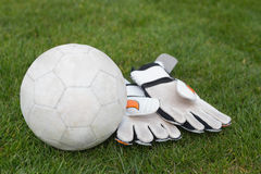 Goalkeeping gloves and football on pitch Stock Photography