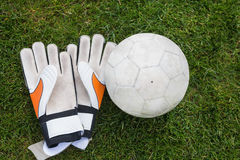 Goalkeeping gloves and football on pitch Stock Photos