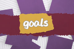 Goals against purple paper strewn over notepad Royalty Free Stock Image