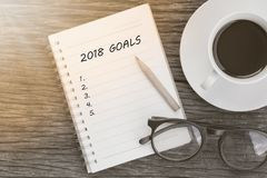 2018 Goals concept on notebook with glasses, pencil and coffee c. Up on wooden table Royalty Free Stock Photos