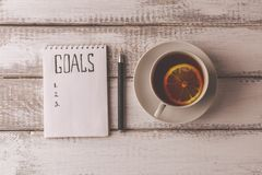 Goals concept. Notebook with goals list, cup of tea on wooden table. Motivation. Strategy write idea success solution concept. Top view. Retro toned image Royalty Free Stock Image