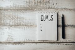 Goals concept. Notebook with goals list tea on wooden table. Motivation. Goals concept. Notebook with goals list on wooden table. Motivation strategy write idea Royalty Free Stock Image