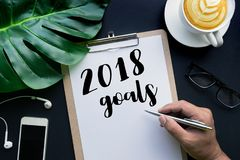 2018 goals concepts with hand writing on notepaper and business accessories. Laying on black table.flat lay/top view Stock Photos