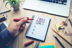 2018 GOALS concepts with male hand writing on notepad paper. On wooden table and supplies Royalty Free Stock Photos