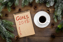 Goals list for 2018. Notebook near spruce branches and pine cones on wooden background top view.  Stock Photography