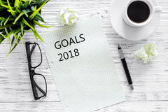 Goals list for 2018. Sheet of paper near pen, glasses and cup of coffee on grey wooden background top view mockup. Goals list for 2018. Sheet of paper near pen Stock Image