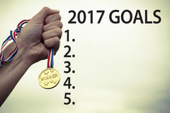 Goals for new year 2017 motivational success concept. Goals, aspirations, resolutions, plans for new year 2017 list with a hand holding medal royalty free stock photography