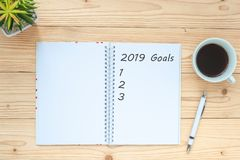 2019 Goals with notebook, black coffee cup, pen and glasses on table, Top view and copy space. New Year New Start, Resolutions, So royalty free stock photo
