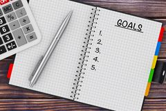 Goals Planning Concept. Calculator, Pen and Organizer with Goals. Sign on a wooden table. 3d Rendering Stock Photography