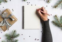 Goals plans dreams make to do list for new year christmas concept writing. In notebook. Woman hand holding pen on notebook with fir branches gift on white stock photography