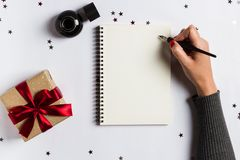 Goals plans dreams make to do list for new year 2018 christmas concept writing. In notebook. Woman hand holding ink pen on notebook with gift red bow on white stock images