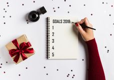 Goals plans dreams make to do list for new year 2018 christmas concept writing. In notebook. Woman hand holding ink pen on notebook with gift red bow on white royalty free stock photos