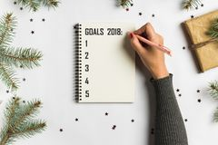 Goals plans dreams make to do list for new year christmas concept writing. In notebook. Woman hand holding pen on notebook with fir branches gift on white royalty free stock images